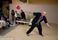 A man loses his grip on the bowling ball during his back-swing in this humorous stock photo about the unexpected and accidents.