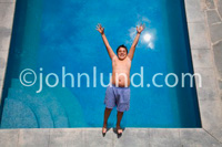 Picture of a young hispanic boy falling backwards into a swimming pool. Overweight chubby young boy having fun in the swimming pool.