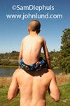 A young boy is sitting on his father's shoulders outside by the lake. Both father and son are bare backed, and the boy is wearing swim trunks. Dad is waist up. Picture from rear.