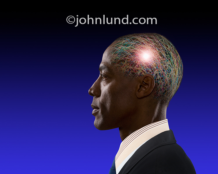 Creativity, innovation and the thought process are all concepts illustrated by this stock photo of a man's head filled with chaotic colored light trails and a bright central glow.