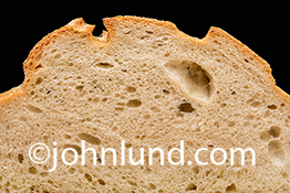 The texture of bread is emphasized in this tight shot of a slice of French bread on a cutting board.