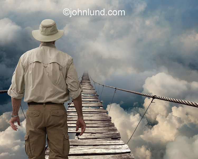 A man stands in contemplation before a dangerous looking cable foot bridge, with missing boards, that disappears into the clouds in an image that is a metaphor for the unknown, mystery, adventure and risk.