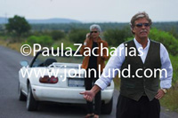A senior couple, man and wife, are stranded on the side of the road. The distinguished looking man has his thumb out for hitch hiking. Small white convertible sports car. Wife on her cell phone in the background.