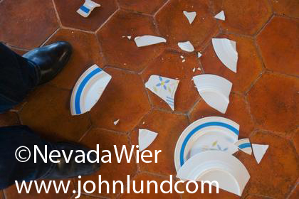 Broken pieces of a dinner plate on the floor at a mans feet. Pair of mens shoes and cuffs with broken china scattered around on the floor  around his shoes. Broken china pic.