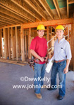 Picture of home builders. Photo of dudes in hard hats in a building under construction. The dudes, an architect and a construction worker are posing for the camera. Picture of two men wearing yellow hard hats at a job site for new construction.