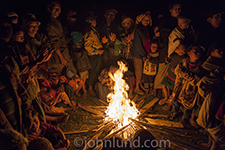 Photo of a gathering of Burmese tribal members around a campfire at night.