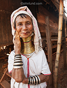 A Burmese tribal woman wears neck rings in her village in an exotic and adveture travel stock photo.