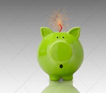 A green piggy bank wears an expression of concern as a fuse on his back spews out sparks in a stock photo about the dangers of green investment.