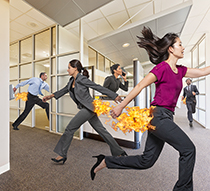 Five business people are highly motivated with their butts on fire as they race through and office in a humorous stock photo about corporate business issues.