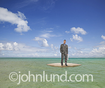 A businessman, holding a briefcase, is stranded on a small sand island surrounded by the ocean  in an image about business challenges and the way forward.