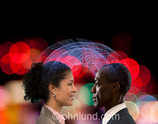 A business man and woman are connected with light trails against the backdrop of city lights at night in a stock photo about connection, networking, and wireless communications technology.
