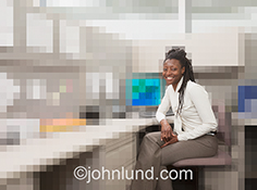 Business in the digital age is seen in this stock photo of an African Amercian businesswoman seat in a digitized virtual office.