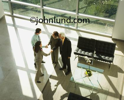 Business people, men and women, shaking hands and making introductions in a lobby.  Four people, two men and two women reaching for each others hands to shake. One man is a senior with gray hair.