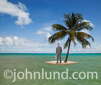 A business man stands on a small sand island under a single palm tree, in the middle of an ocean in an image about isolation, challenge and business concepts.