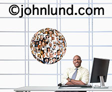 A successful African American business executive sits back in his modern upscale office enjoying the moment as next to him is a sphere of portraits in a metaphor for a social media business network.