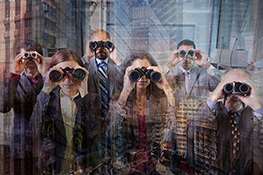 A group of five business executives or professionals stand atop a mountain peaking rise up through the clouds and search with binoculars for opportunities, deals, and dangers.