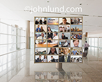 Photo of a video display with multiple screens in an airport setting depicting business people and global business meetings.