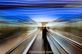 Business travel and speed are the concepts behind this stock photo of a business person zooming along an escalator through an unidentifiable airport or public space. The image has a futuristic and high tech feel including vivid blue colors overhead reinfo