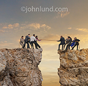 Two teams of business people engage in a tug of war at the edge of cliffs on either side of a deep chasm in a photo about teamwork, adversity and challenge.