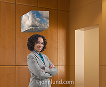 A businesswoman is connected to the cloud in this stock photo of a woman dressed in business attire and standing beneath a