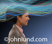 A business woman's head is surrounded by flowing colored streaks of light in an image about connections, business connections, and networked and wireless communications technology.