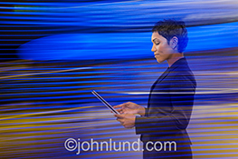 A business woman stands with tablet in hand as she is enveloped in streask of light indicating technology connections and networking.