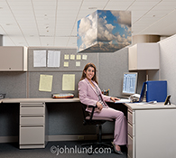 Successful cloud computing is illustrated in this stock photo of a smiling businesswoman sitting in her office beneath a