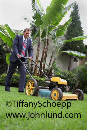 Businessman In Coat And Tie Mowing His Lawn With A Gas
