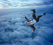 A businessman falls through the sky towards cloud cover below in a stock photo about risk, danger, and, surprisingly, falling in to cloud computing.