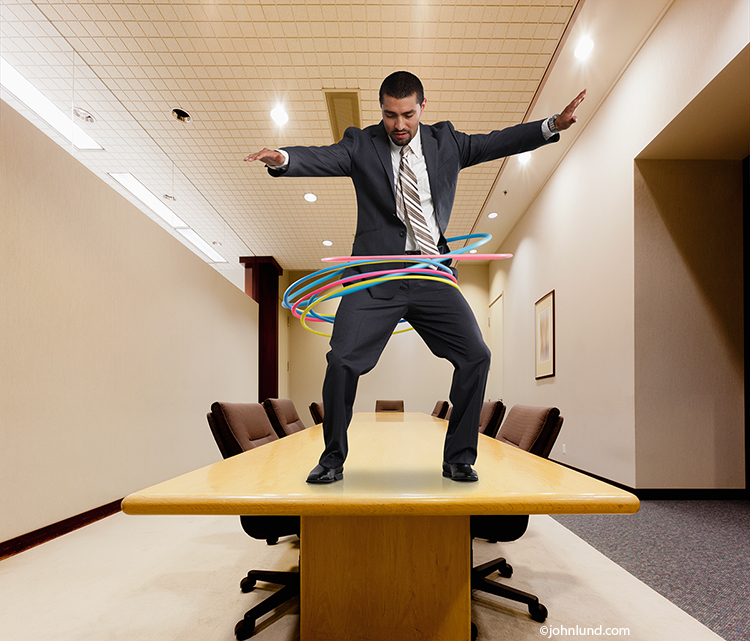 A latino businessman stands on a boardroom table hula hooping with multiple hoops in a humorous stock photo about business concepts, presentation training and business challenges.