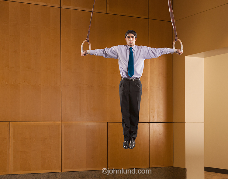 The business skill and dedication required for success are the concepts illustrated in this stock photo of a businessman performing the iron cross on gymnastic rings in a corporate environment.