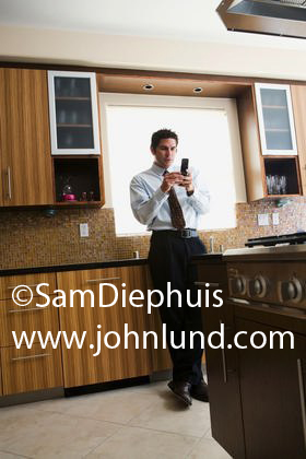 Texting on his cell phone a businessman is in his kitchen leaning against the counter next to the kitchen sink.