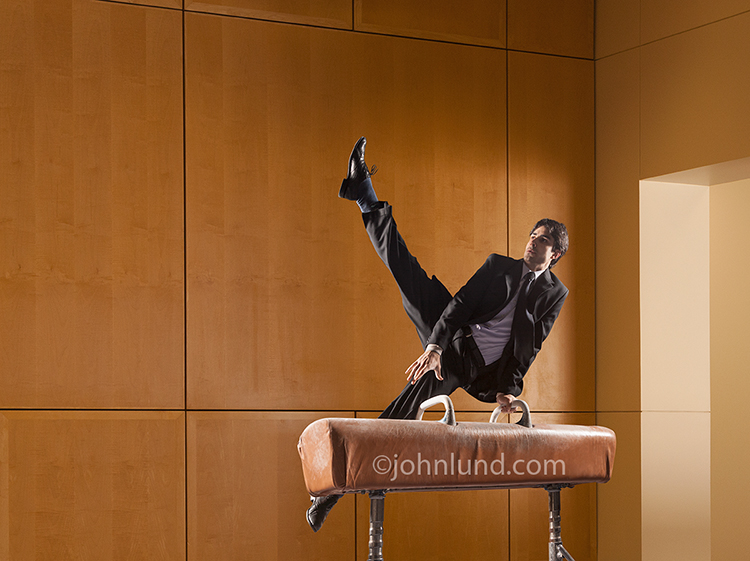A businessman demonstrates skill and success as he performs a gymnastic routine on a pommel horse in a corporate setting...while wearing a coat and time, in this business stock photo.