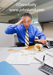 Photo of an Asian or Chinese American man spilling a cup of coffee right in the middle of his desk ruining the paperwork spread out in front of him. Bad day at the office. Pics of office accidents.