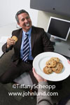Stock photo of an executive or businessman accepting a cookie from a plate of cookies being passed out to office workers. Snacktime at work. Advertising picture of a man with a cookie in his office. Fun at the office.