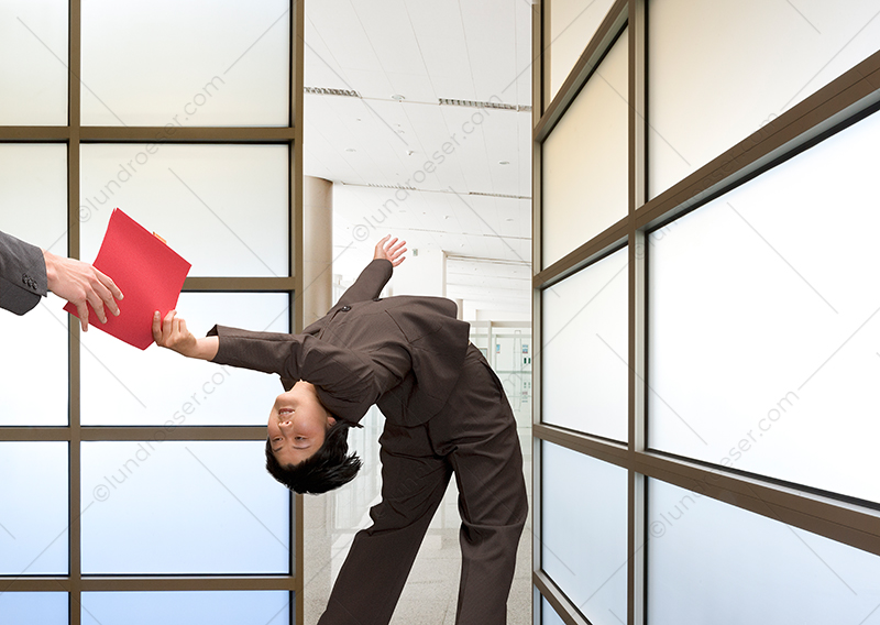 A businesswoman bends over backwards to hand off a file folder in a stock photo about business, service, and teamwork.