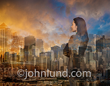 A woman executive contemplates the future as she looks out over a composite cityscape made up of buildings from around the world and an uplifting sunrise in a business montage stock photo.