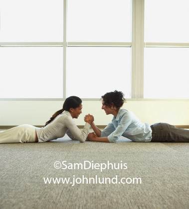 Image of a couple of businesswomen or office workers having an arm wreslting match on the office floor at work. Picture of competitive women at work.