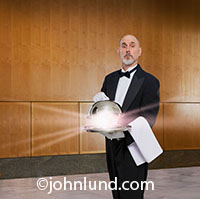 Rays of light stream out from under a the cover of a silver tray being held by a butler in an upscale wood-paneled room.