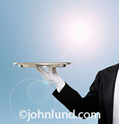 In this photo a butler holds an empty silver tray outdoors...an invitation for special service that is yet to be determined.