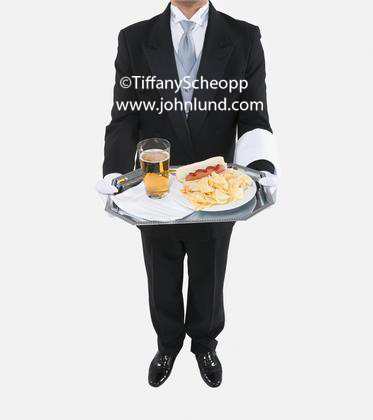 Butler pictures. This pic of a butler standing holding with a sliver tray balanced on his finger tips and the other hand behind his back. The Butler has on white gloves and a tuxedo. He also has a white towel over his arm. Butler pics for ads.