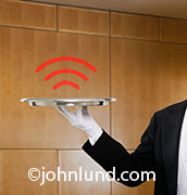 A wireless hot spot is indicated with a set of bars hovering over the silvery tray held by a butler in an image about wireless connections and future communications technology.