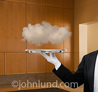 A butler serves up a cloud on a tray in a metaphor for cloud computing and all that entails from connection, to neworking to online computing.