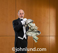 A butler stands in an upscale wood-paneled lobby holding a silver tray with money flowing out over the edges in a stock photo about abundance and cash flow.
