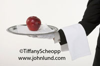 Photo of a delicious ripe red apple on a white napikin on a silver serving tray being held by a white gloved butler's hand. The butler has a white towel draped over his arm. Pic of a butler bringing an apple. White background.