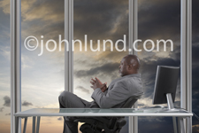 Picture of an African American executive gazing out the windows of his corner office contemplating gathering storm clouds.