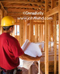 Picture of a construction worker with his back to the camera and holding a set of blue prints. The worker has a yellow hard hat on his head and is wearing a red shirt. The man is standing in the middle of a bunch of framing for a new home.