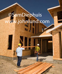 Stock photo for ads of two construction workers or carpenters carrying wooden beams into a building under construction. The workmen are wearing hard hats and the bulding is a two story building.  Large construction project pics.