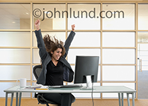 A woman, hair flying, throws up her arms and grins in a celebration of her business success as she sits in front of her computer in an upscale office.