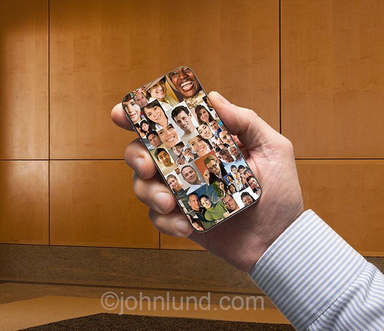 A businessman's hand holds a cell phone filled with a composite image of multiple social media portraits in a stock photo about social networking, connections, distributed workforces, and wireless technology.